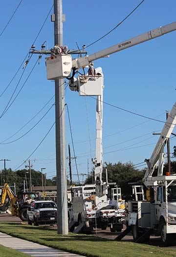Power crews repairing storm-damaged power lines